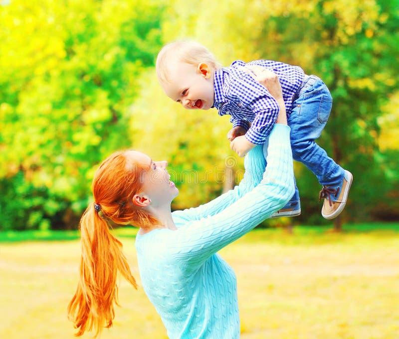有儿子孩子的俏丽的母亲获得乐趣一起户外 免版税库存照片