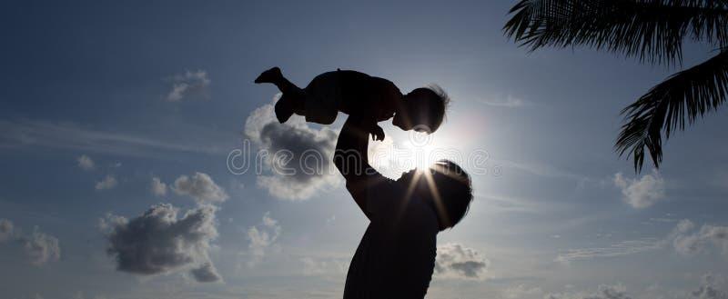 有儿子的剪影父亲 免版税库存照片