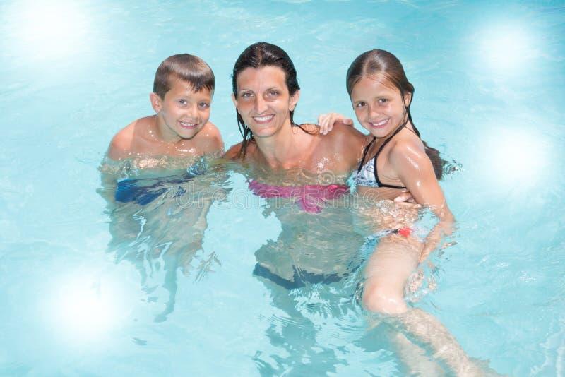 有儿子的单亲母亲和女儿在水池夏天使用 库存照片