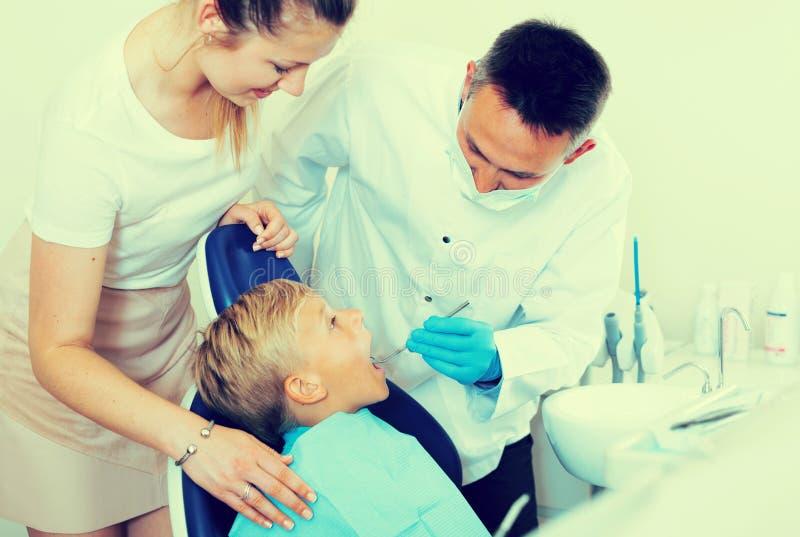 有儿子的女性拜访牙医 图库摄影