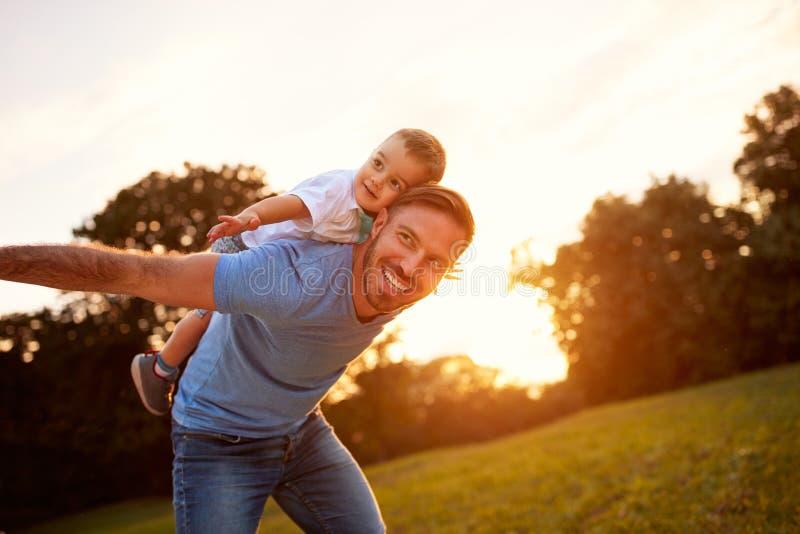 有儿子的愉快的年轻父亲在公园 免版税图库摄影