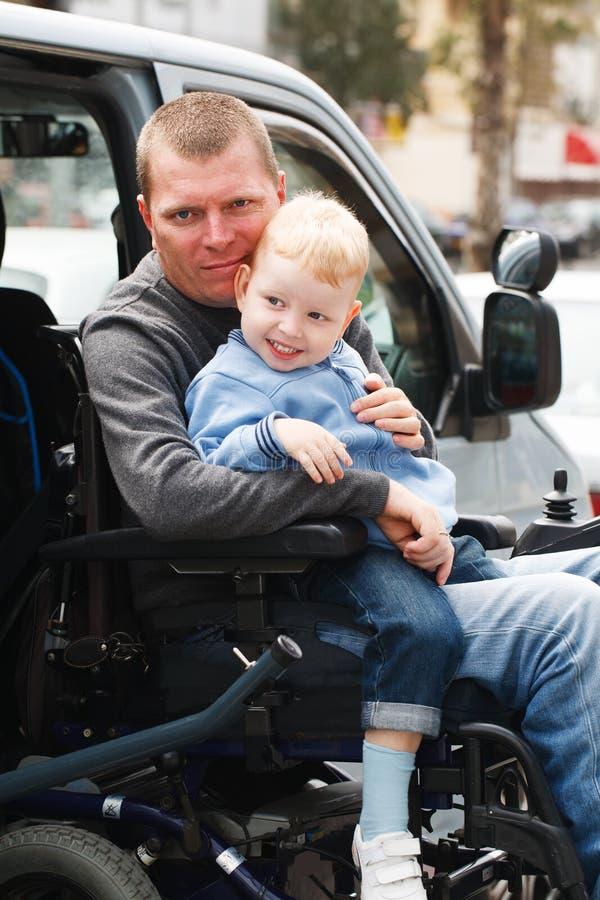 有儿子的残疾人轮椅升降式的 库存照片