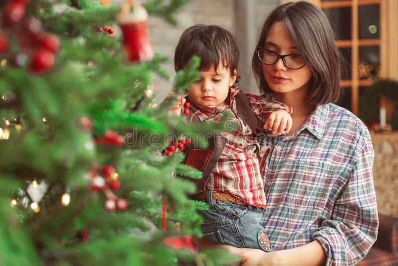 有儿子的母亲在圣诞树附近 图库摄影