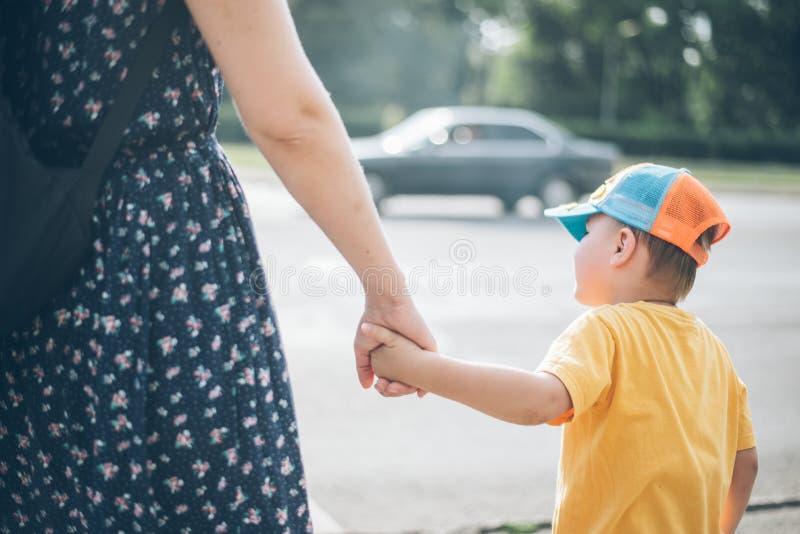 有儿子的母亲在红绿灯站立 免版税图库摄影