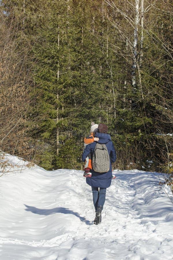 有儿子的母亲走沿积雪的路的胳膊和背包徒步旅行者的以具球果森林冬日为背景 库存图片