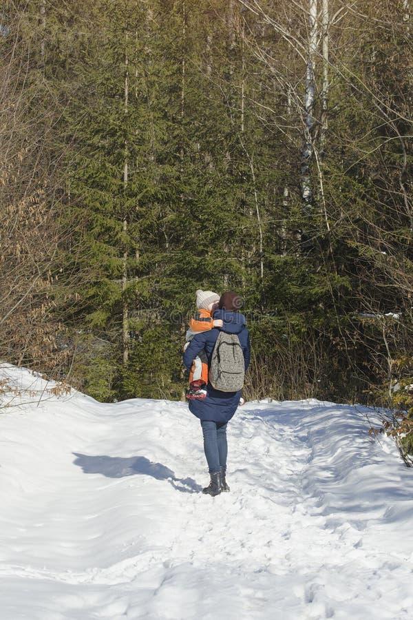 有儿子的母亲走沿积雪的路的胳膊和背包徒步旅行者的以具球果森林冬日为背景 库存照片