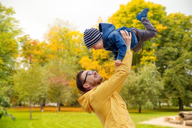 有儿子的父亲演奏和获得乐趣在秋天 免版税库存图片
