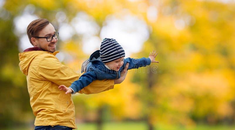 有儿子的父亲演奏和获得乐趣在秋天 免版税库存照片