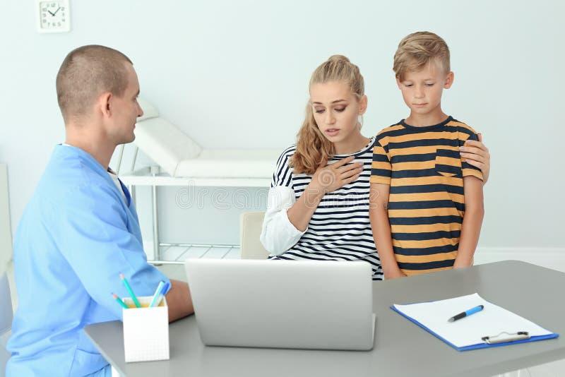 有儿子的男性医学助理咨询的母亲 库存照片