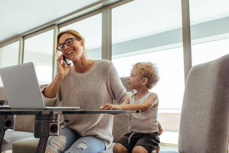 有儿子的繁忙的妇女在家庭办公室 库存图片