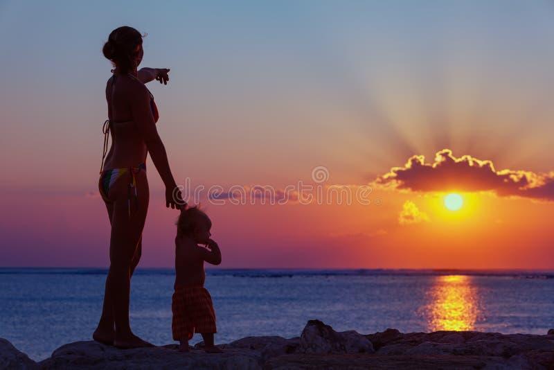 有儿子看看的母亲在海滩的日落太阳 库存照片