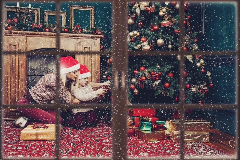 有儿童佩带的圣诞树的母亲在新年前 免版税库存照片