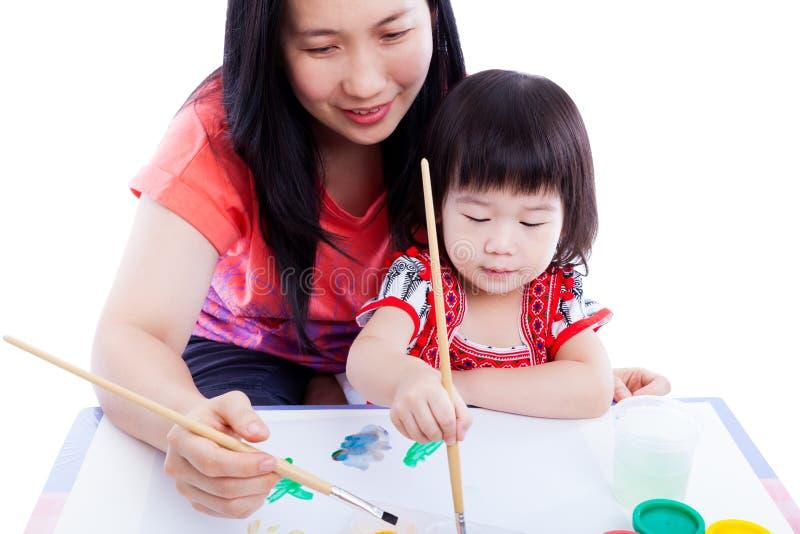 有儿童女孩使一致和油漆的母亲 隔绝在丝毫 免版税库存图片