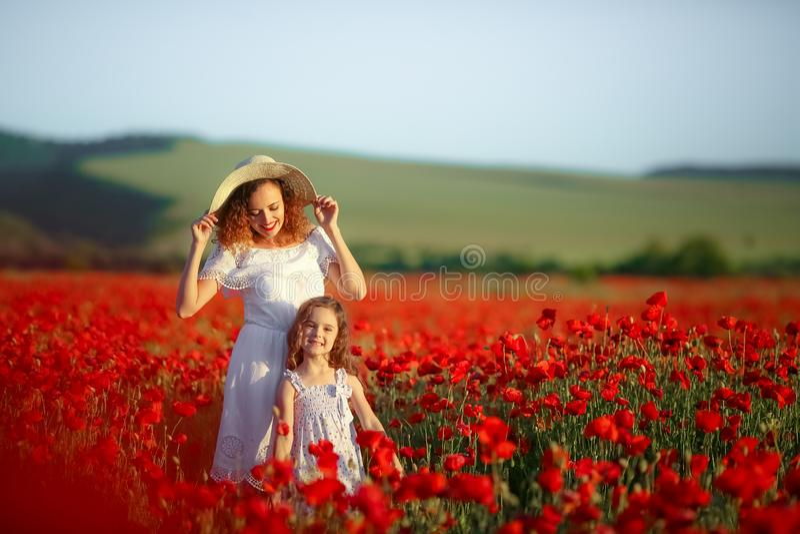 有儿童女孩的美丽的年轻女人鸦片领域的 幸福家庭获得乐趣本质上 在鸦片的室外画象 免版税库存图片