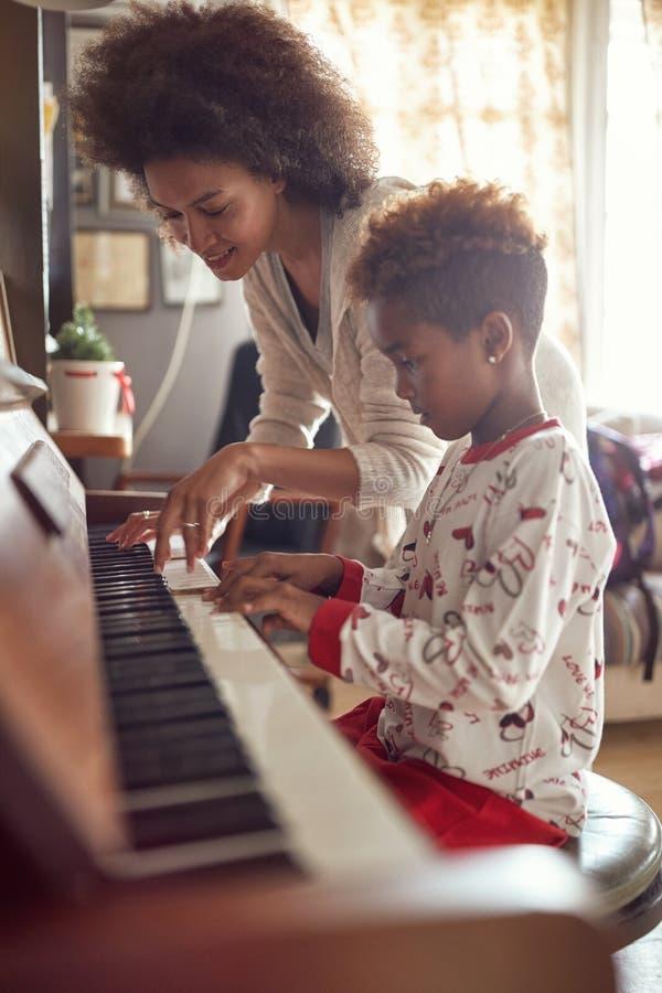 有儿童女孩的非裔美国人的母亲圣诞节戏剧音乐的 免版税库存照片