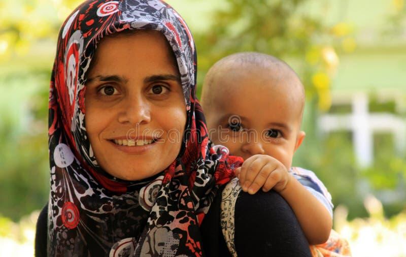 有儿童微笑的回教母亲 免版税库存照片