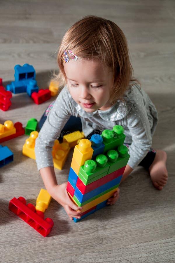 有儿童的女孩明亮的塑料建筑块乐趣和修造  使用在地板上的小孩 开发的玩具 早learni 免版税库存图片