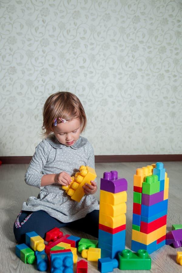 有儿童的女孩明亮的塑料建筑块乐趣和修造  使用在地板上的小孩 开发的玩具 早learni 库存图片