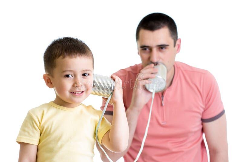 有儿童的男孩和的爸爸与锡罐的一个电话 免版税库存照片