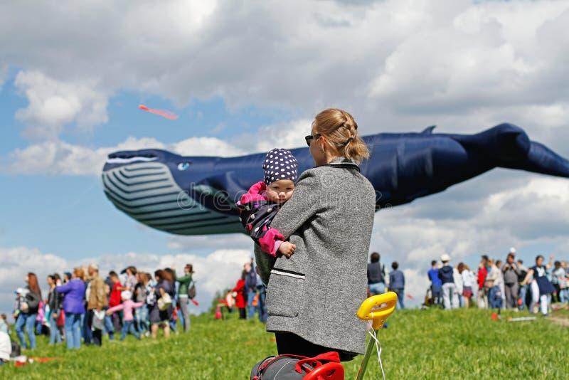 有儿童立场的母亲以在风筝节日的一只巨大的鲸鱼风筝为背景在公园Tsaritsyno在莫斯科 库存图片