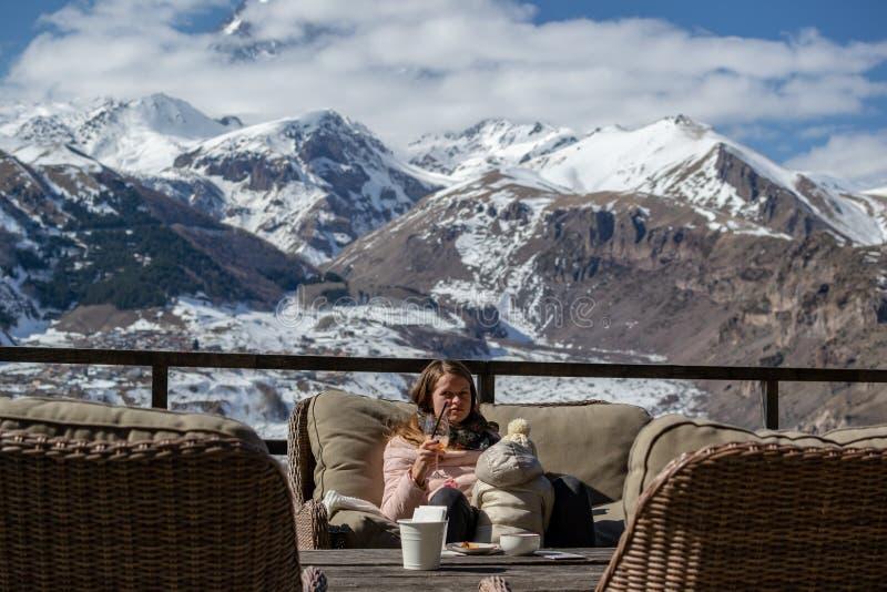 有儿童饮料apperol鸡尾酒的年轻女人在旅馆大阳台有风景山景在卡兹别吉,乔治亚 库存图片