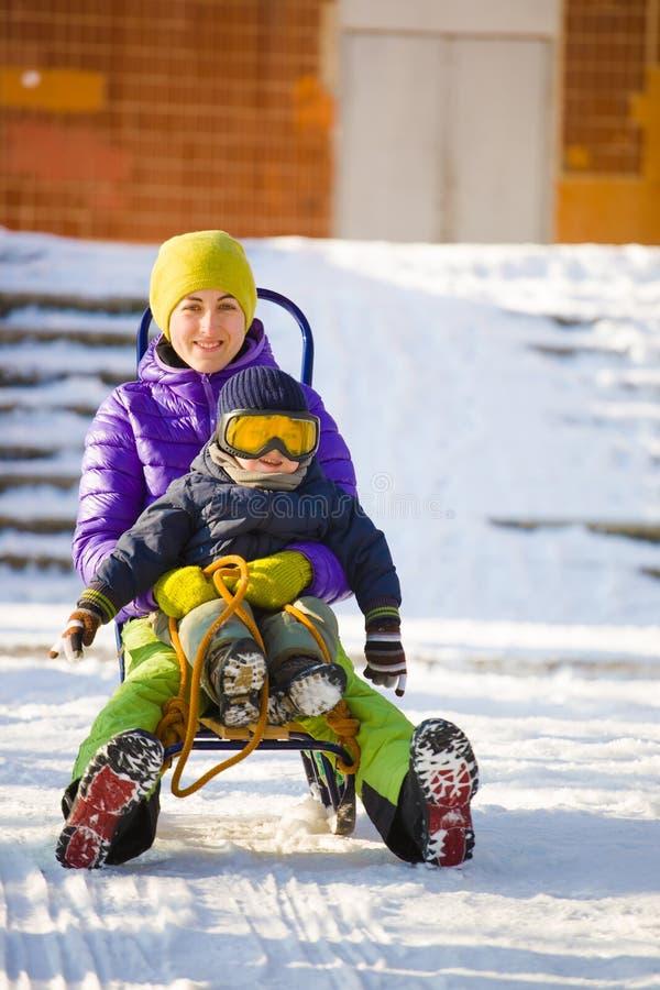 有儿童sledding的一个妈妈 免版税图库摄影