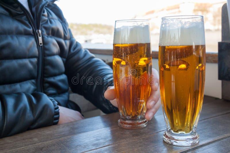 有充分的杯的男性手低度黄啤酒 免版税库存照片