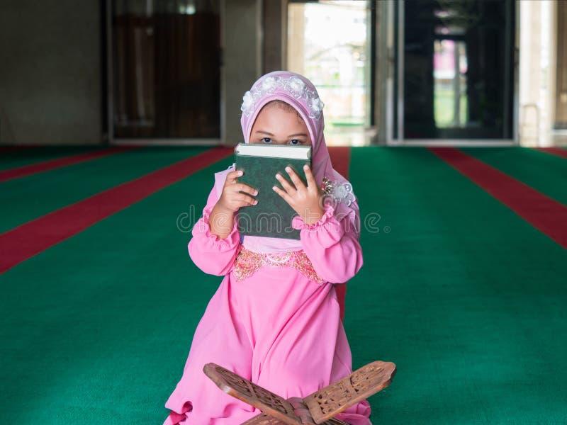 有充分的hijab的愉快的回教女孩在桃红色礼服 免版税图库摄影