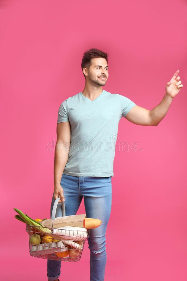 有充分篮子的年轻人在桃红色背景的产品 免版税库存照片
