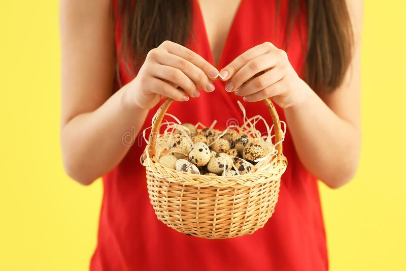 有充分篮子的年轻女人复活节的鹌鹑蛋,特写镜头 免版税库存照片