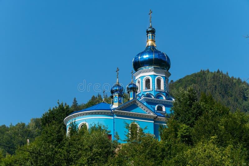 有光亮的蓝色的一个美丽的教会在阳光下与站立在树绿色丛林的圆顶反对 库存照片