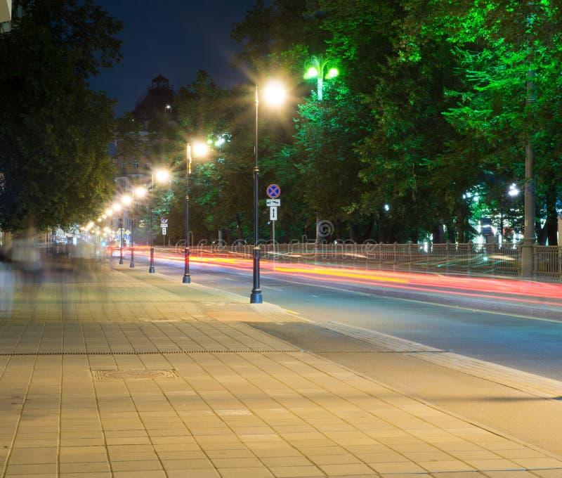 有光和交通的城市街道在晚上 背景,城市生活 免版税库存照片