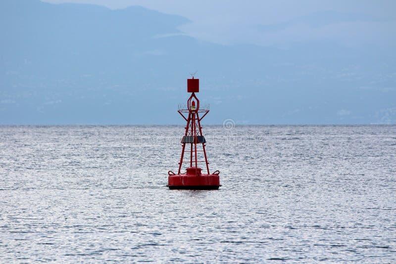 有光的红色航行浮体在充电的顶面和小太阳电池板被围拢的与不安定的海 库存照片