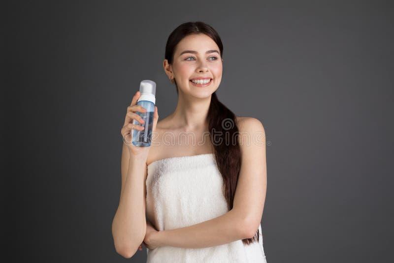 有光秃的肩膀举行的逗人喜爱的典雅的微笑的妇女和有泡沫的当前化妆瓶 免版税库存图片