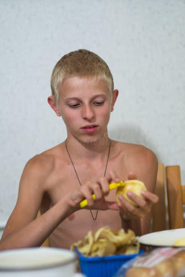 有光秃的躯干的少年剥土豆 免版税图库摄影