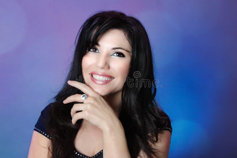 有光滑的黑发和大愉快的微笑的美丽的妇女 免版税库存照片