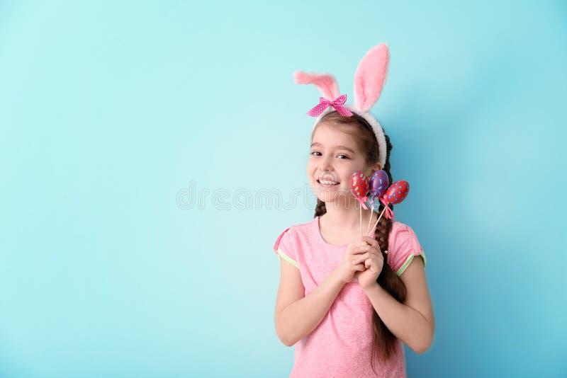有兔宝宝耳朵和复活节彩蛋的逗人喜爱的女孩在颜色背景 库存照片