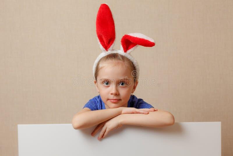 有兔宝宝耳朵和空白的横幅的美丽的小女孩 愉快的复活节 图库摄影