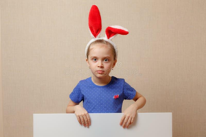 有兔宝宝耳朵和空白的横幅的美丽的小女孩 愉快的复活节 库存图片