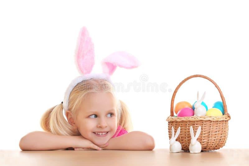 有兔宝宝耳朵的充分逗人喜爱的小女孩和篮子在背景的复活节彩蛋 免版税库存照片