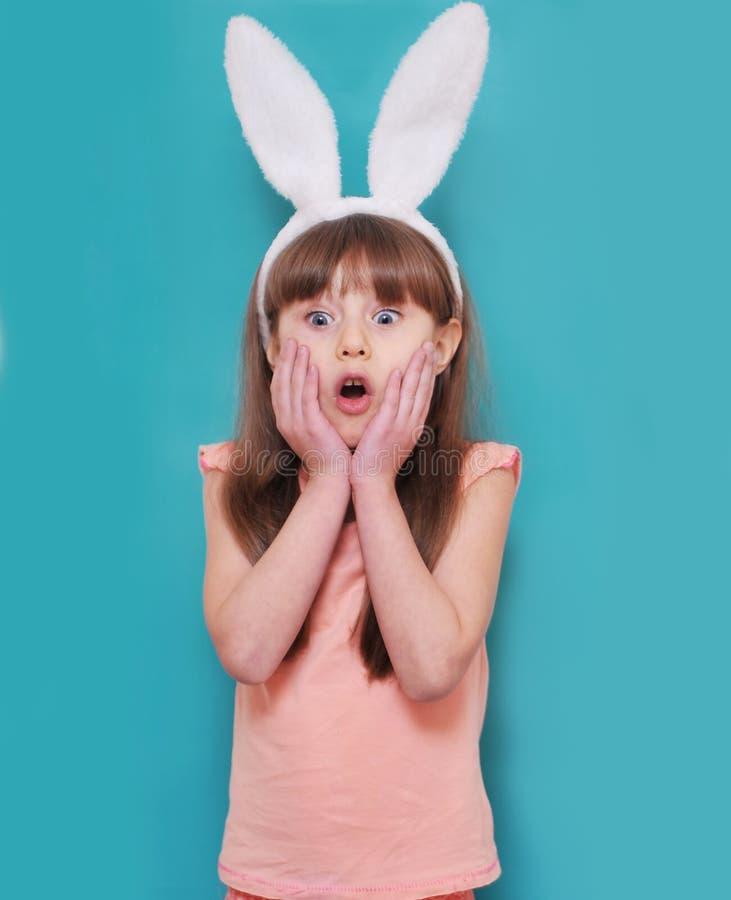有兔宝宝耳朵的逗人喜爱的女孩拿着鸡蛋 免版税库存照片