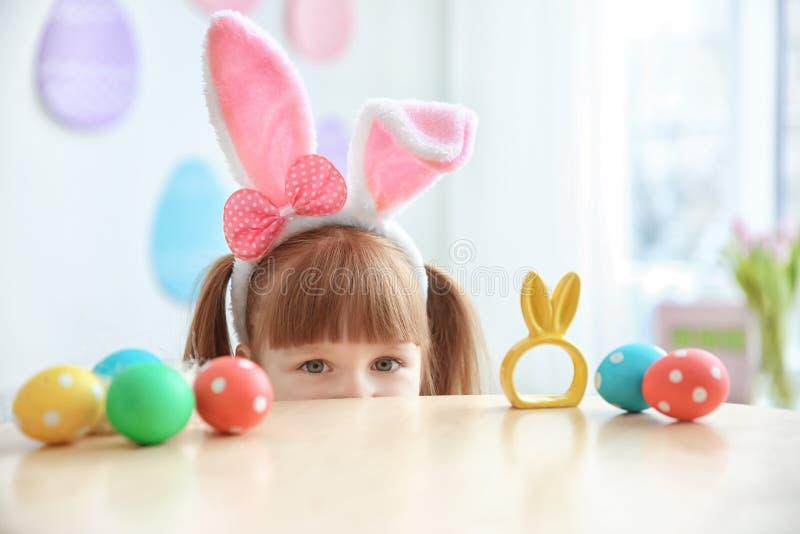 有兔宝宝耳朵的逗人喜爱的小女孩临近桌用复活节彩蛋 免版税库存照片