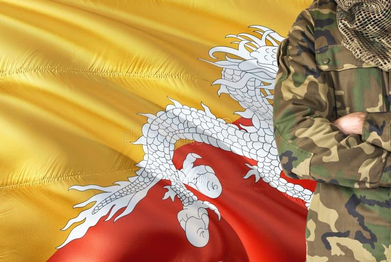 有全国挥动的旗子的横渡的胳膊不丹战士在背景-不丹军事题材 库存图片