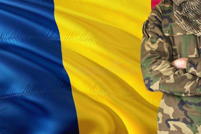 有全国挥动的旗子的横渡的胳膊乍得战士在背景-乍得军事题材 免版税图库摄影