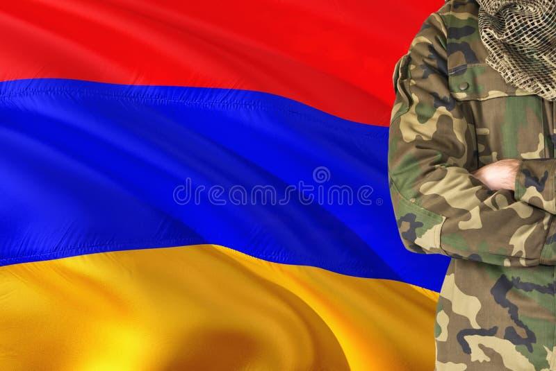有全国挥动的旗子的横渡的胳膊亚美尼亚士兵在背景-亚美尼亚军事题材 库存图片