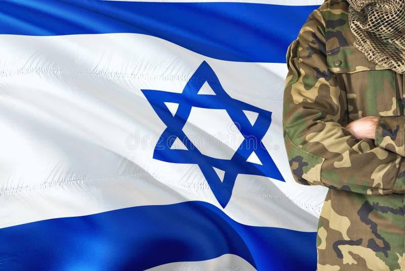 有全国挥动的旗子的横渡的胳膊以军士兵在背景-以色列军事题材 库存图片