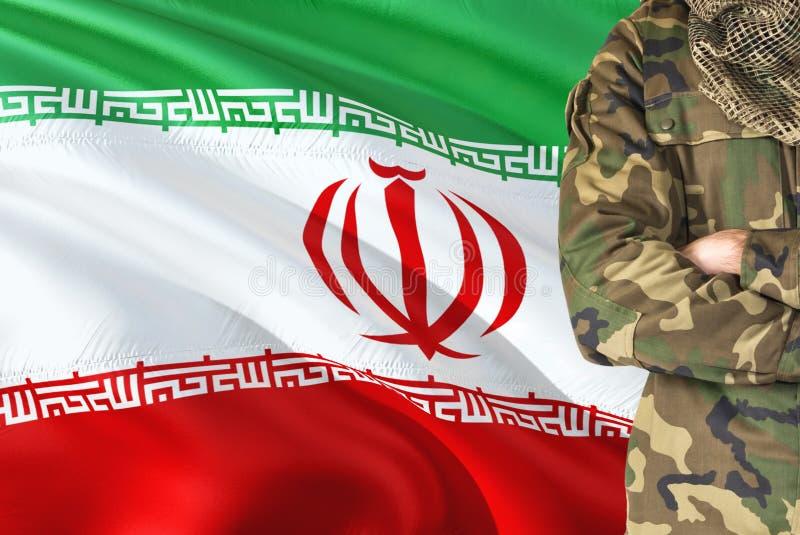 有全国挥动的旗子的横渡的胳膊伊朗士兵在背景-伊朗军事题材 免版税库存照片