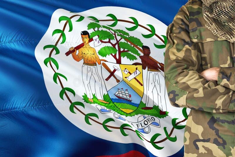 有全国挥动的旗子的横渡的胳膊伯利兹人士兵在背景-伯利兹军事题材 免版税库存图片