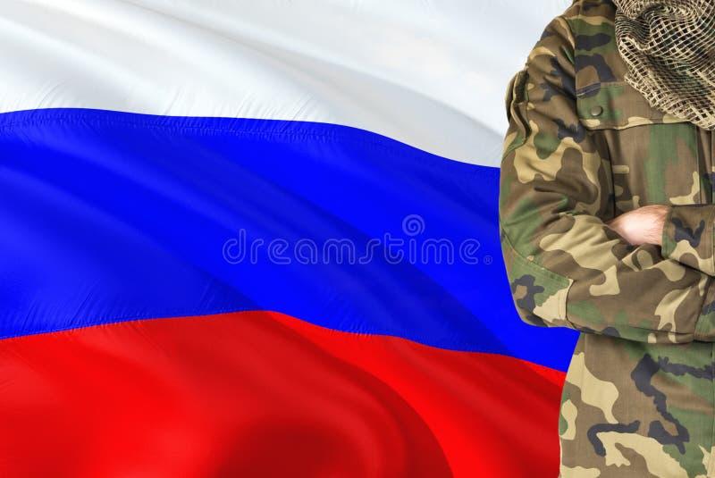 有全国挥动的旗子的横渡的胳膊俄国士兵在背景-俄罗斯军事题材 免版税库存照片