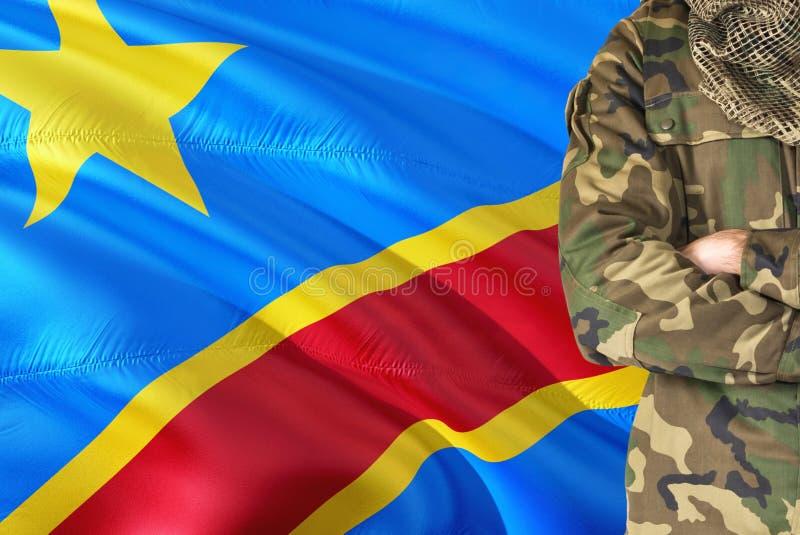 有全国挥动的旗子的横渡的胳膊刚果士兵在背景-刚果军事题材 库存照片